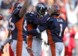 Denver Bronco quarterback Jake Plummer, middle, hugs teammate and kicker Jason Elam, right, as ...
