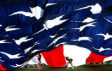 Junior Bronco cheerleaders help hold up an American Flag during pre-game of the Denver Bronco...