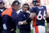 Denver Bronco head coach Mike Shanahan, middle, has words with center Tom Nalen, right, after the...