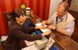 (Denver, Colo., May 24, 2004) Front Desk Clerk Anna Marie Martinez, helps Norman Godfrey, of...