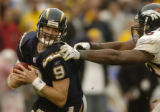 (San Diego, CA, December 5, 2004)  Drew Brees runs out of the grasp of Reggie Hayward in the third...