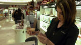 Beauty advisor Michaela Minter puts foundation into sample bottles at Flatiron Crossing shopping...