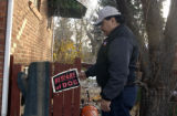 (Denver, Colo. Nov. 24, 2004)  Larry Griego examines the beware of dog sign which was hanging on...