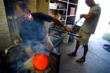 (DENVER, Co., SHOT 9/14/2004) Denver glassblower Kit Karbler (left) works on glass lighting...