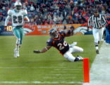 (DENVER, CO., DECEMBER 12, 2004)  Denver Broncos #26, Tatum Bell, right, trips and falls out of...