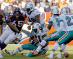 (DENVER, CO., DECEMBER 12, 2004)  Miami Dolphins #91, Jay Williams, center, comes down with an...