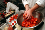 (DENVER, Co., SHOT 11/22/2004) Tomatoes are tossed with oil and basil before being oven roasted in...