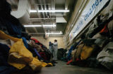 (Denver, Colo., 12/2/ 2004)  Volunteer Gracelda Romo sorts coats at Dependable Cleaners' ...
