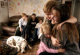 [LAKEWOOD, CO - Shot on: 12/21/04] Anna Davis hugs Daden, 8 and Gillian, 2  with her other...
