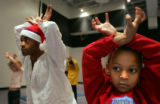 12/22/2004 DENVER, COLORADO-Jacque Howard, 6, right, practices her best reindeer in a movement...