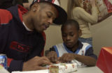 (DENVER, Colo., December 23, 2004) Mr. Camby works on final wrapping with Andre Camack, 11, as he...