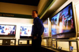 [DENVER, Colo.,  Jan. 12, 2005) Soundtrack employee Tony Grant stands among big screen television...