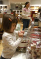 (BROOMFIELD, Colo. Nov. 23, 2004) Peyton Roby, 3, looks into a bin of trinkets while her mother,...