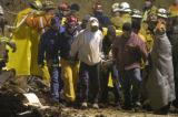 La Conchita 1.12.04: Rescue workers, friends and relatives of a man who lost his wife and three of...