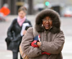 Candy Bell (cq) bundles up from the cold at the corner of Broadway and 17th Monday afternoon April...