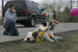 On the shoulder of the highway Brandon Goodrich,(cq) a jr. at Horizon HS kneels next to a memorial...