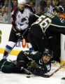 Stars Willie Mitchell (2) tries to get to the puck in front of teammate Sergi Zubov (56) and Avs...