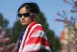 Veronica Guerrero (cq), 18, wears an American Flag in a march along Speer Wednesday, April 19,...