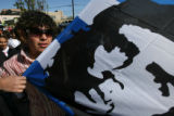 Westminster High School student Christian Hernandez, 15, marches with a flag of Che Guevera...