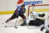 The Colorado Avalanche's Ian Laperriere (#14) has the puck poke checked away from him by the...