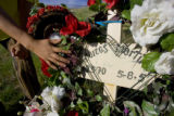 The hand of Enedina Martinez, CQ, reveals her husbands name on a marker at the spot where her...