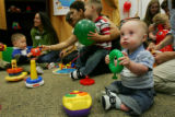 Daniel Walshe, 11 months old, right, and other developmentally delayed children, play with toys at...