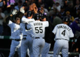 Colorado Rockies teammates mob Matt Holliday (#5) after Holliday scored from third base to win the...
