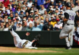 Colorado Rockies' starting pitcher Jason Jennings (#32) falls onto first base for a force out to...