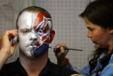 Avalanche and Nuggets fan Chris Potts (cq, left) of Denver gets his face painted in each team's...