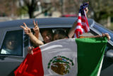 Young men wave Mexican and U.S. flags out the window of their car to show support to a group of...