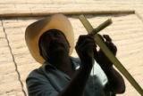 Catalino Valdivia, 48, of Denver makes a cross out of a palm before Palm Sunday Mass at St....