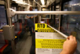 George Sweeney (cq) a 6 year employee with RTD removes a strike advisory from the interior of a...