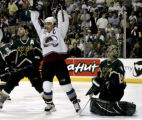 Avs Joe Sakic (C) celebrates between Stars Sergi Zubov (L) and goalie Marty Turco after...