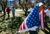 Efrain Ramirez (cq), 30, of Colorado Springs drapes himself in the American flag as he marches...