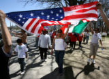 Viviana Romirez (cq) (center), 19 of Aurora, carries the Mexican flag with her sister Roxana, 18,...