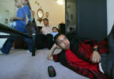 Raul Miranda Jr.,CQ, 12, right, watches television while his sister Janet Miranda, CQ, 8, left,...