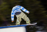 A snowboarder boardslides a rail at Echo Mountain Park near Evergreen as his pants hang close to...