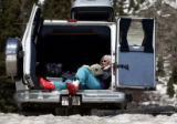 Jill Mickey, cq, Wawatosa, Wis., reads in the back of her van after skiing at Arapahoe Basin ski...