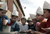 First graders from the Lower School of Herzll / RMHA at the Denver Campus  grind wheat as they...
