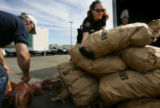Lakewood police agent (cq--agent), Erin Zimmerman (cq), right, helps load potatoes onto a truck at...