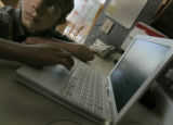 On April 13, 2006, in Lafayette, Colo. Ryan Sapena, (cq) 11 works on his laptop at home after...