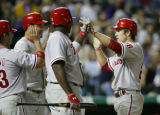 Chase Utley, right, is congratulated by (from left) Aaron Rowand, Pat Burrell, and Ryan Howard...