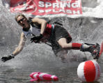 Snowboarder Julie Fredlake goes down in the frigid pond of water during the 38th annual Winter...
