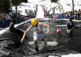 Snowboarder Marc Schiechl climbs out of the pond during the 38th annual Winter Park Resort Spring...