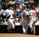 Rockies Aaron Cook, center, tags out Phillis Chase Utley, right, at first base after getting the...