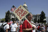 "Counter protester Dave Gusky (cq) from Denver carries a sign through the crowd during a "" We..."