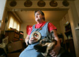 Portrait of Lee Zuberer (cq), 65, with her seeing-eye dog, Vida, as she holds a picture of her...