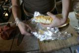 Dinner co-op member Tami McGuan (cq), unveils one of her burritos that she will chop up for people...