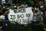 "A group of fans hold a banner saying ""Bonds is bad for baseball"" as Barry Bonds takes..."