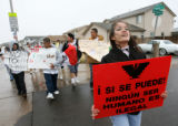 "Montbello High School senior Beta Barrera (right) carries a sign that reads ""Yes we can! No..."
